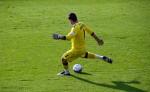 a goalie kicks a soccer ball